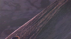 A man climbs up a steep slate of rock. Stock Footage