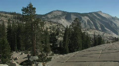 Trees stand among mountains and rocky hillsides at Yosemite Stock Footage
