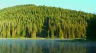 Steam moves across Trillium Lake which is surrounded by Stock Footage