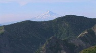 A snow-capped mountain rises above a forest at Mt. St. Stock Footage