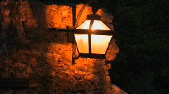A light fixture attached to a stone wall is on at night. Stock Footage
