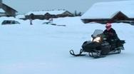 A snowmobile rides his snowmobile through a town. Stock Footage