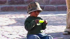 A Latin American boy sits on the ground and eats a green Stock Footage