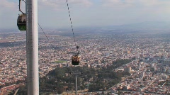 People are transported via cable car high above a city. Stock Footage