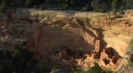 A cliff rises above Pueblo Indian dwellings in the Mesa Verde National Park, Stock Footage