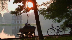 People sit in a park in Hanoi at sunset and admire the view. Stock Footage