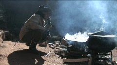 A Chinese cowboy sits by a fire and smokes. Stock Footage