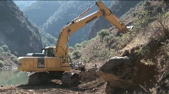 A steam shovel moves earth along a rural road. Stock Footage