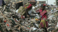 A woman and a girl child are picking through waste paper. Stock Footage