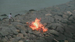 A man throws something into a fire. Stock Footage