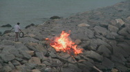 Stock Video Footage of A man throws something into a fire.