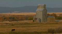 A grain silo sits on a grassy plain. Stock Footage