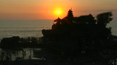 Stock Video Footage of The sun silhouettes the Pura Tanah Lot temple in Bali, Indonesia.