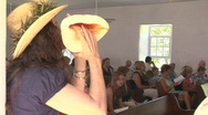 A woman blows a conch shell during a church service in Hawaii. Stock Footage