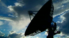 A satellite dish moves in time lapse and is silhouetted Stock Footage