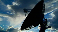 Stock Video Footage of A satellite dish moves in time lapse and is silhouetted