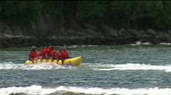 A group of young people wearing red life jackets ride Stock Footage