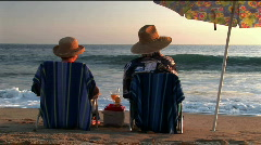 An elderly couple share drinks under an umbrella on the beach. Stock Footage