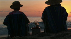 A couple toasts the ocean as they sit on a beach. Stock Footage