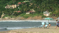 Three people walk to the water at a beach resort. Stock Footage