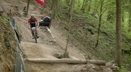 Cyclist race along a rough dirt road course. Stock Footage