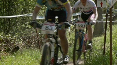 A group of mountain bikers race up a courses trail. Stock Footage