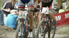 Off road cyclists race up a dirt inclined road. Stock Footage
