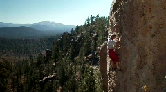 A man climbs up the side of a mountain. Stock Footage