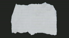 A crumpled piece of paper flattens out. Stock Footage