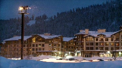 A snowplow passes in front of a hotel in a mountain resort. Stock Footage