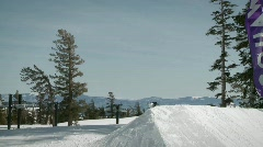 A snowboarder makes a jump off a mound of snow. Stock Footage