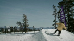 A snow boarder hits a bank of snow and gets air. Stock Footage