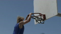 A man dunks a basketball and hangs on the rim for awhile. Stock Footage