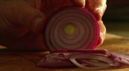 A man slices a red onion on a cutting board. Stock Footage