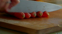 A chef slices carrots with a knife. Stock Footage