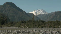 Slow move out of a dry river bed and snow capped peak in Stock Footage