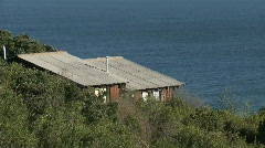 A cabin sits on a bluff overlooking the ocean near Curanipe, Chile. Stock Footage