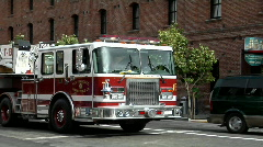A hook-and-ladder fire truck turns a corner in an urban area. Stock Footage