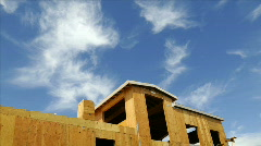 Stock Video Footage of Time-lapse of clouds blowing above a house under construction.