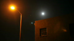 Time lapse of moon rising over a house and street lamp. - stock footage