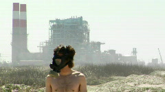 A man in a gas mask stands in front of a power plant. Stock Footage