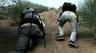 A woman and man wearing backpacks struggle to climb up a Stock Footage