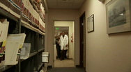 Stock Video Footage of Medical personnel walk through a hallway.