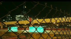 Traffic passes under a freeway overpass at night. Stock Footage