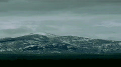 A storm gathers around a snow capped mountain. Stock Footage