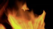 Stock Video Footage of Bright orange flames flicker in a blazing fire.