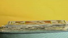 Newspapers stack up on a table in time lapse. Stock Footage