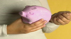 A woman places coins into a piggy bank. Stock Footage