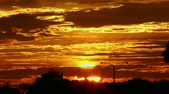 The sun glows behind clouds in a red and orange sky. Stock Footage