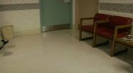 A nurse wheels an empty wheelchair through a hospital lobby. Stock Footage